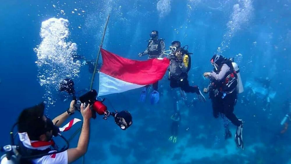 pramuka penyelam kibarkan bendera merah putih